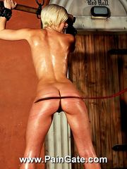 Horny busty blonde painslave is hanged up nude for a serious ass and back whipping torture.